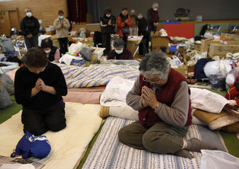A minute of silence is held by victims of the March 11 earthquake and tsunami at a shelter in Kamaishi, Iwate prefecture.