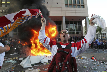 A Canucks fan waves a Canadian and British Columbia flag in front of an overturned burning pickup truck during riots in downtown Vancouver, British Columbia