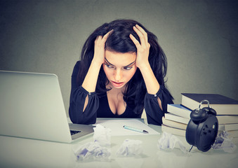 Too much work stressed woman sitting at her desk with books in front of laptop