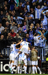 Malaga's Sanchez is congratulated by teammates after scoring against AC Milan during their Champions League soccer match at La Rosaleda stadium in Malaga