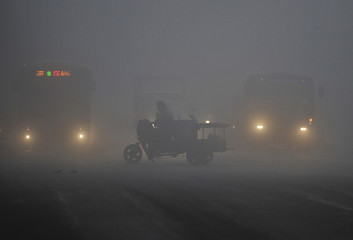 A tricycle travels past a crossroad on a hazy day in Hefei