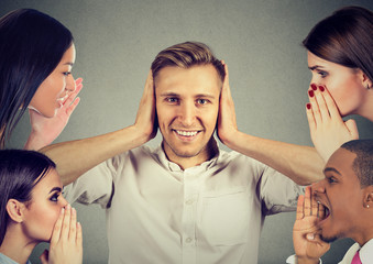 people whispering a secret gossip to a man who covers ears ignoring them