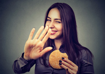 woman with hamburger rejecting advise on healthy eating