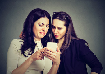 Two upset friends women viewing on line content on a smart phone