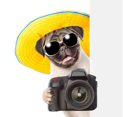 Dog photographer in summer hat and sunglasses peeking from behind empty board and taking pictures. isolated on white background