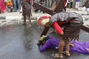A man playing the role of Jesus Christ lies on a road during a ritual procession re-enacting the death of Jesus in Lagos