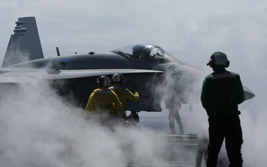 An F/A 18 Hornet, which runs on biofuel gets ready for flight ops on the USS Nimitz during the RIMPAC Naval exercises off Hawaii .