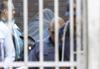 Police escort one of three suspects accused of killing a British tourist as they arrive in a court in Cape Town