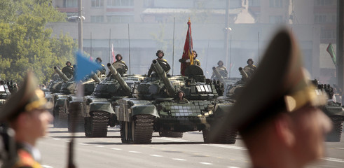 Serviceman take part in a military parade, as Belarussian army vehicles move in the background, during celebrations marking Independence Day in Minsk