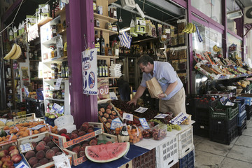A customer buys fruits in a grocery market in central Athens
