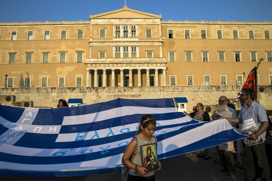 A girl holds an icon next to a Greek flag during a protest against the construction of the first official mosque in Athens