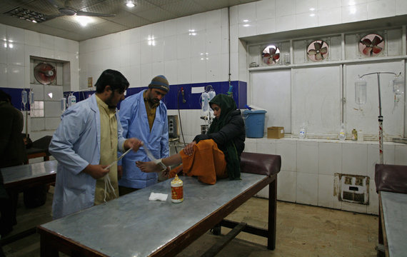 A doctor treats a patient's leg at a hospital in Quetta