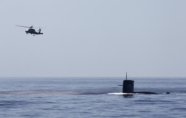 An S-70C helicopter flies over a submarine during the Han Kuang military exercise held about 10 nautical miles eastern of the port of Hualien