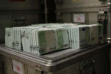 Wads of 100 euro banknotes are stacked in a pile at the Money Service Austria company's headquarters in Vienna
