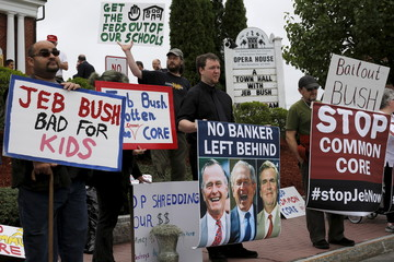 Protesters hold signs outside a campaign town-hall meeting with Republican presidential candidate Jeb Bush in Derry