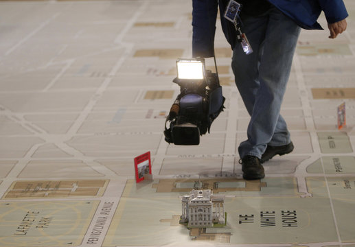 A news videographer films a model of the White House on a large map at the DC Armory in Washington