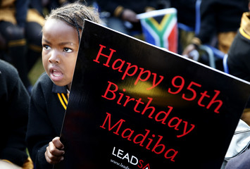 Children hold placards as they gather to wish to former President Nelson Mandela happy birthday at a township school in Atteridgeville near Pretoria