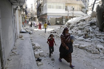 Civilians walk near a destroyed building after a Syrian Air Force fighter jet launched a bomb in the city of Aleppo