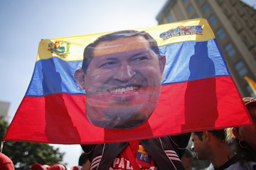 A supporter of Venezuelan President Chavez waves a flag with a picture of Chavez during a  gathering outside Miraflores Palace in Caracas
