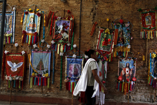 A woman walks past religious icons hanging on a wall during celebrations for Sao Jorge's day in Rio de Janeiro