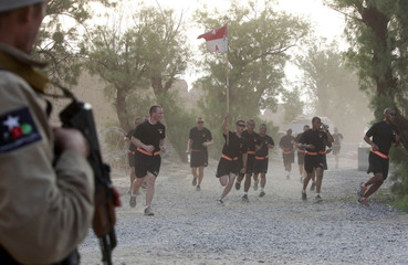 U.S. soldiers from Task Force Bronco run past an Afghan guard during a memorial run to commemorate the 10th anniversary of the 9/11 attacks, at a U.S. military camp FOB Shinwar in Nangarhar