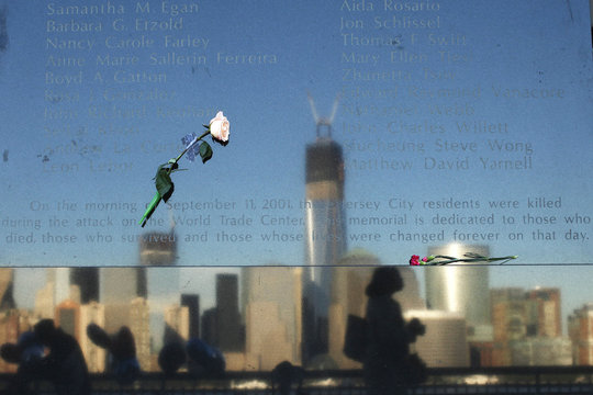 People are reflected in a memorial monument during events marking the 11th anniversary of the 9/11 attacks on the World Trade Center in Exchange Place in New Jersey
