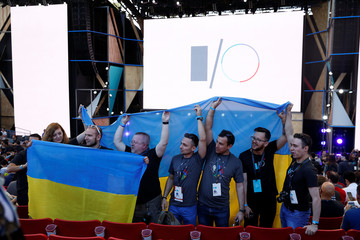 A group of attendees stand for a photo while holding a Ukrainian flag during the Google I/O 2016 developers conference in Mountain View, California