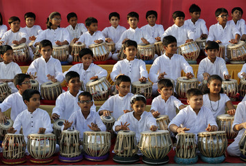 Students play the tabla, an Indian percussion instrument, during the annual tabla competition held in a park on the banks of the Sabarmati river in Ahmedabad