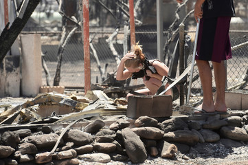 Brittany Thompson cries after finding a deceased dog at a burned down residence after the Erskine Fire burned through South Lake, California