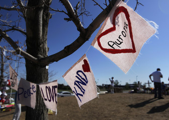 Signs drawn on fabric are seen hanging from a tree at a memorial for victims behind the theater where a gunman opened fire on moviegoers in Aurora