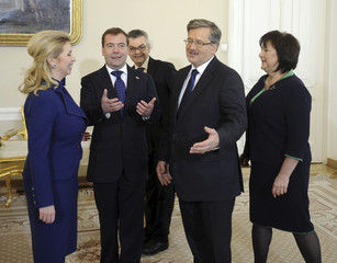 Russian President Medvedev Polish President Komorowski and wives talk after posing for a photo at the Presidential Palace in Warsaw