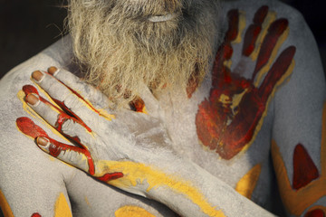 A Hindu holy man applies paint on his body at Pashupati Temple in Kathmandu
