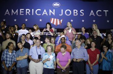 Participants on stage gather under an American Jobs Act banner after U.S. President Barack Obama spoke at West Wilkes High School in Millers Creek