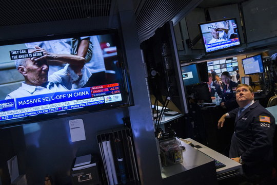 A trader works on the floor of the New York Stock Exchange as news related to the falling stock market in China is shown on a television screen shortly after the opening bell in New York