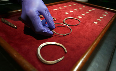 A curator holds one of three silver arm-rings that metal-detectorist, James Mather, discovered as part of a Viking Hoard, which  included silver ingots and rare coins of King Alfred of Wessex and King Ceolwulf II of Mercia, at the British Museum London