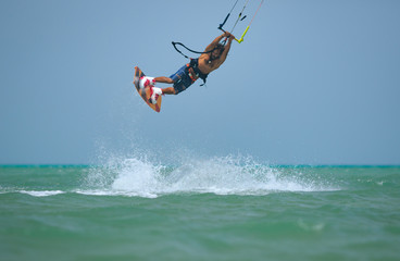 Kite boarding sportsman jumping high with kite and huge water splash and kiteboard in blue sky, active sports and life style, recreation hobby and fun, rider man on the simple air background
