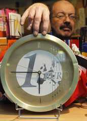 A shopkeeper adjusts a clock with the euro symbol outside the EU Council building ahead of an European Union summit in Brussels