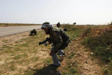 Rebel fighters take cover under fire in eastern Libya