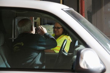 A motorist takes a photo of toll collector Dean at the Golden Gate Bridge toll plaza in San Francisco