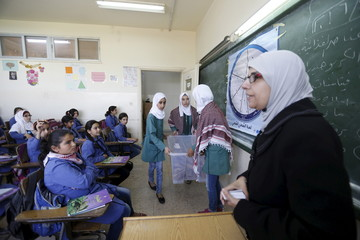 A teacher distributes meals to students as part of a WFP-run project to provide healthy meals to students and to raise awareness of good eating habits, at Hofa Al-Mazar school  in the city of Irbid