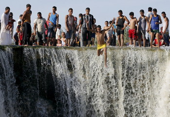 Youth jumps from a waterfall in Wadi El-Rayan, near the end of the summer vacation at the desert of Al Fayoum Governorate
