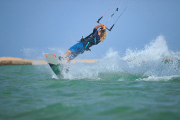 Professional kitesurfing rider sportsman jumps high acrobatics kiteboarding back mobe trick  with huge water splash. Recreational activity and extreme active water sports, hobby and fun in summer time