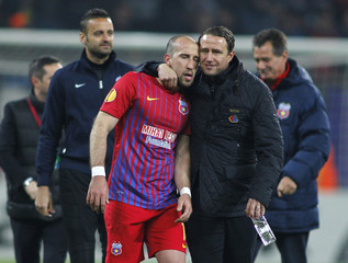 Steaua Bucharest's head coach Reghecampf celebrates with his player Latovlevici at the end of their Europa League soccer match against Chelsea in Bucharest
