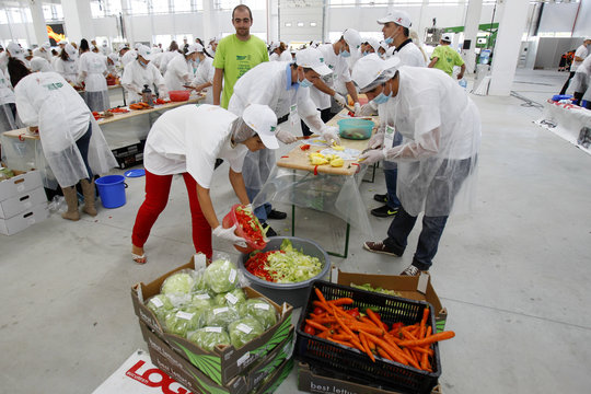 Volunteers prepare vegetables to create the world's biggest vegetable salad during a Guinness World Record attempt in Pantelimon