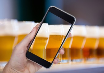 Hand of person taking a picture of beers  with her smartphone