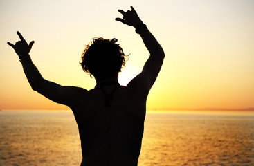 Man silhouette on the sea background, sunset time