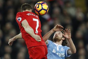 Stoke City's Joe Allen in action with Liverpool's James Milner