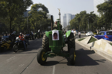 Farmer drives a tractor with a picture of one of the 43 missing trainee teachers during a protest in Mexico City
