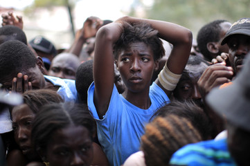 A woman waits in line during a food distribution near the presidential palace in Port-au-Prince, Haiti