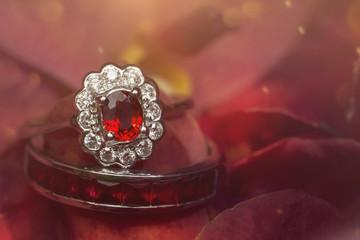 red gemstone ring on rose